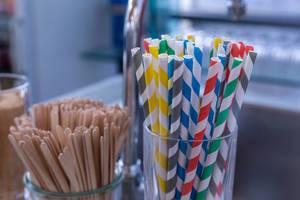 Bunte Papier-Trinkhalme und Holzstäbchen in Gläsern bei einem Buffet