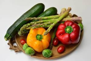Bunte Paprika, Zucchini, grüner Spargel, Rosenkohl und Kirschtomaten auf Tonteller