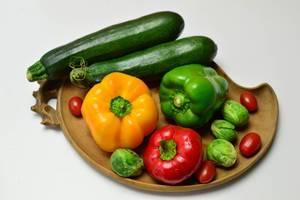 Bunte Paprika, Zucchini, Rosenkohl und Kirschtomaten auf Tonteller auf weißem Hintergrund