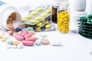 Bunte Pillen und Arznei-Kapseln in Tablettenpackungen, auf einem weißen Tisch gestreut