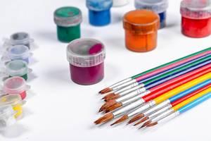 Bunte Pinsel und verschiedene Farbtöpfe als Zeichenset auf weißem Untergrund