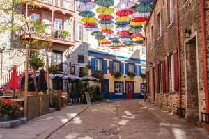 Bunte Regenschirme über einer leeren Altstadtgasse an einem sonnigen Tag