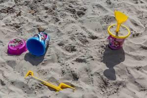 Bunte Sandeimer und Schaufeln am Strand