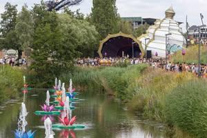 Bunte Seerosebrunnen am See von Tomorrowland Festival mit Party-Leuten im Hintergrund