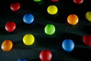Bunte Smarties, Süßigkeiten aus Schokolade mit farbiger Glasur verteilt auf dunklem Untergrund
