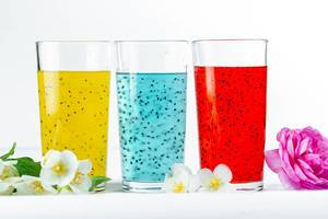 Bunte Sommercocktails in verschiedenen Farben, mit Blumen vor weißem Hintergrund