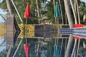 Bunte Sonnenschirme spiegeln sich im Wasser eines Schwimmbads