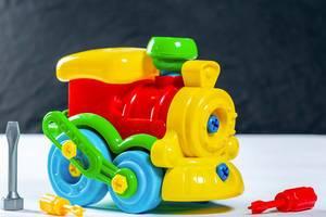 Bunte Spielzeug-Lokomotive aus Kunststoff mit Schraubenschlüsseln auf weißem Tisch