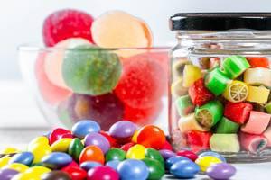 Bunte Süßigkeiten und Bonbons in Gläsern und auf Tisch vor weißem Hintergrund