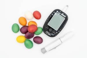 Bunte Süßigkeiten und ein Blutzuckermessgerät vor weißem Hintergrund