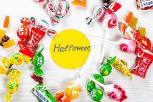 Bunte Süßigkeiten zu Halloween im Kreis angeordnet auf einem weißen Tisch
