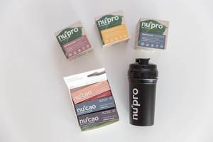 """Bunte Verpackungen der Nu-Company, mit Rohkakao """"NuCao"""", den Proteinshakes """"NuPro"""" und einer schwarzen Trinkflasche für Sportler"""