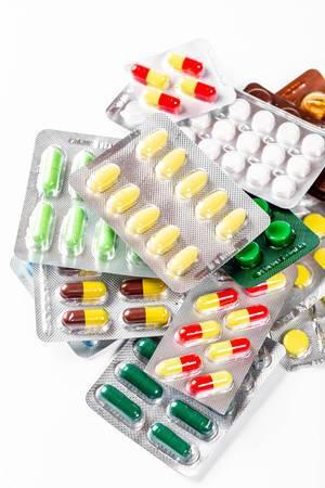 Bunte, verschieden farbige Tabletten und Kapsel in Verpackungen auf einem weißen Untergrund