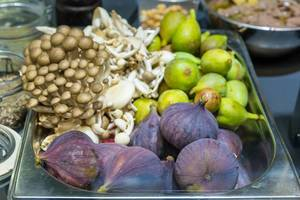 Bunte Zutaten für ein gesundes Mittagessen: Pilze, Feigen und Früchte in einer Aufbewahrungsbox