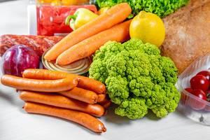 Bunter Einkauf mit Lebensmitteln wie Würstchen, reifer Brokkoli, rote Zwiebel, Möhren, Brot, Tomaten und Konserven