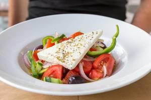 Bunter, griechischer Salat, mit Fetakäse und frischem Gemüse, auf einem weißen Teller