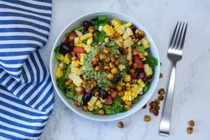 Bunter mexikanischer Salat mit Kichererbsen, Mais und Tomaten in einer weißen Schale