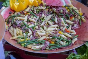 Bunter Penne-Nudelteller als exotisches Mittagessen, mit Bohnen, Schinken, Paprika und Wassermelone
