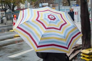 Bunter Regenschirm aufgespannt bei herbstlichen, regnerischen Wetter an einer Straße