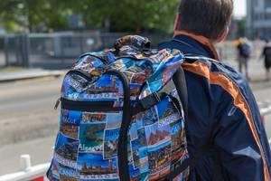 Bunter Reiserucksack mit Fotos von verschiedenen Reisezielen