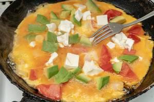 Buntes Frühstück: Omelett mit Avocado, Käse und Tomaten in einer Pfanne
