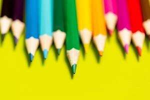 Buntstifte auf gelbem Hintergrund mit Schärfentiefe