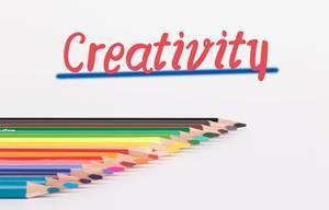 """Buntstifte vor weißem Hintergrund mit rotem """"Creativity"""" Text"""