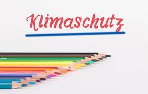 """Buntstifte vor weißem Hintergrund mit rotem """"Klimaschutz"""" Text"""