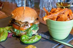 Burger auf einem Holzspieß, mit Tomaten, Salat, Fleisch und Sauce, neben grünen Pepperoni und Süßkartoffel-Pommes im Restaurant