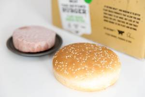 Burger bun in close-up with Beyond Meat plant-based, soy free and gluten free burger patty on black plate