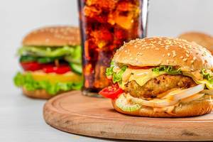 Burger with cutlet, cheese and vegetables with a glass of Coca Cola (Flip 2019)