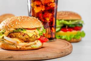 Burger with cutlet, cheese and vegetables with a glass of Coca Cola