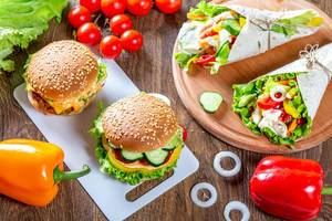 Burgers and pita bread with fresh vegetables on a brown wooden table