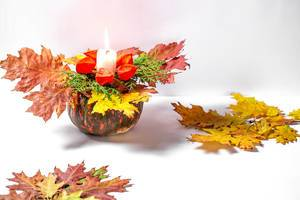 Burning candle in original candlestick with pumpkin and autumn leaves