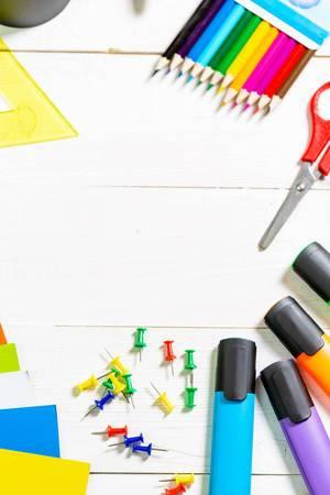 Büro- oder Bastelutensilien mit bunten Textmarkern, Buntstiften, farbigem Papier, Schere und Pinwand-Nadeln