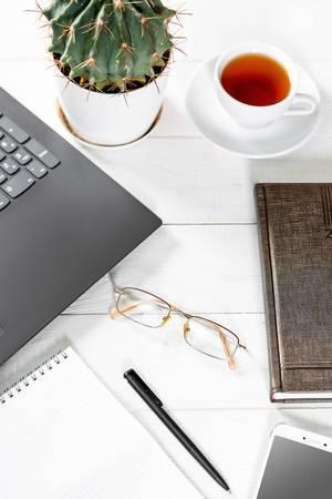 Büroarbeitsplatz mit Laptop, Notizblock, Kalenderbuch, Brille, Mobiltelefon, einer Tasse Tee und Kaktus