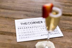 Business card of The Corner Bar advertised breakfast and snacks, next to a blurred champagne glass with strawberry slice , in Barcelona (Spain)
