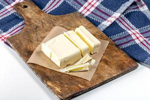 Butter slices on an old kitchen Board with a blue kitchen towel (Flip 2020)