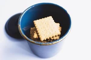 Butterkekse in einem blauen Gefäß auf Porzellan