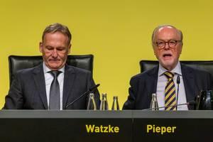 BVB-Chef Hans-Joachim Watzke und Gerd Pieper sitzen hinterm Pult mit Mikro auf der BVB-Hauptversammlung in Dortmund