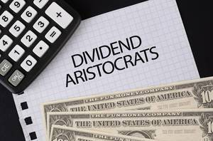 Calculator, money and Dividend Aristocrats text on black table