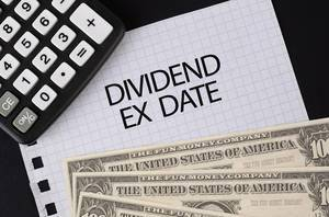 Calculator, money and Dividend Ex Date text on black table