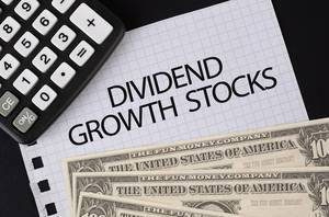 Calculator, money and Dividend Growth Stocks text on black table