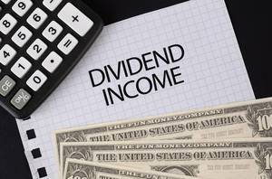 Calculator, money and Dividend Income text on black table