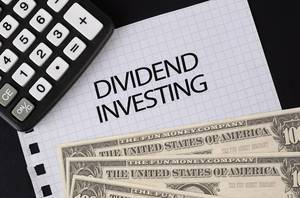 Calculator, money and Dividend Investing text on black table