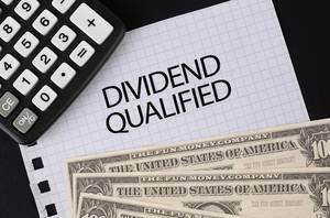 Calculator, money and Dividend Qualified text on black table