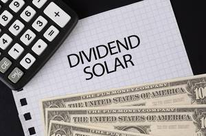 Calculator, money and Dividend Solar text on black table