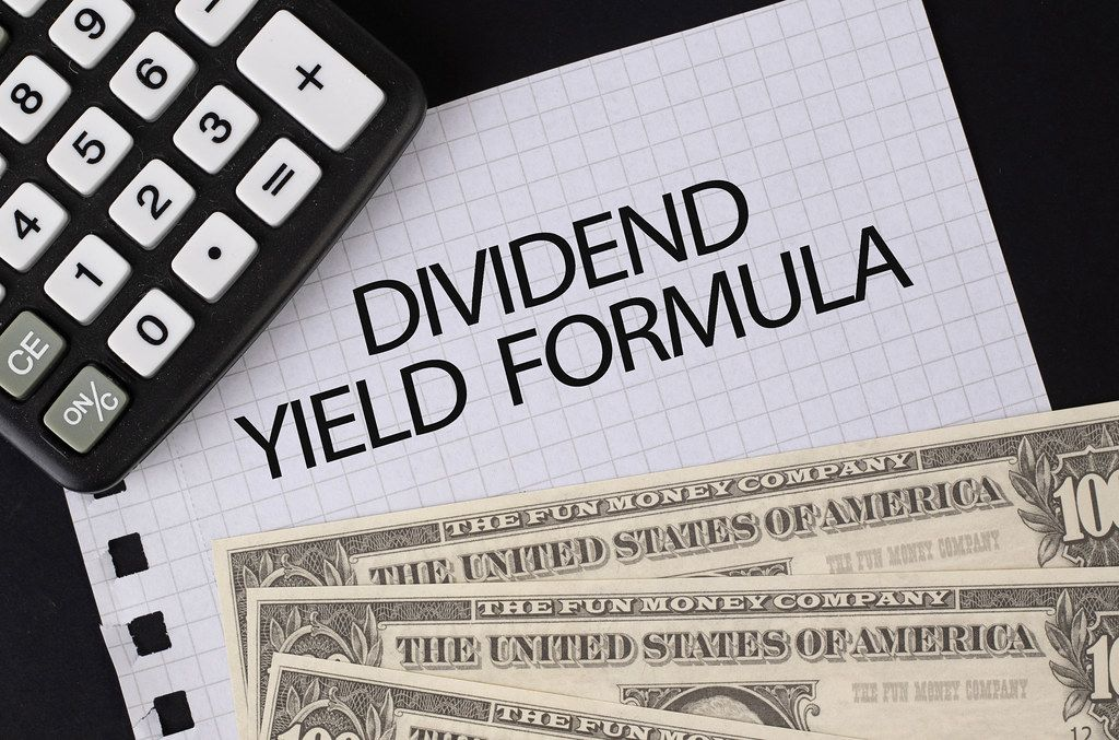 Calculator, money and Dividend Yield Formula text on black table