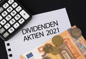 Calculator, money and Dividenden Aktien 2021 text on black table