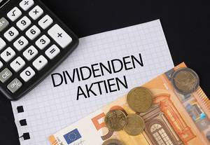 Calculator, money and Dividenden Aktien text on black table